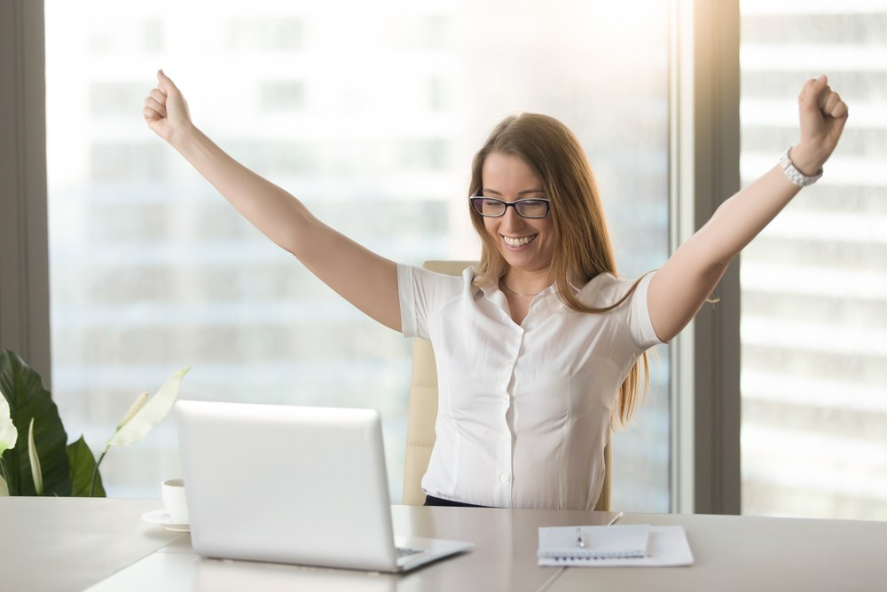 a woman celebrating in front of a laptop