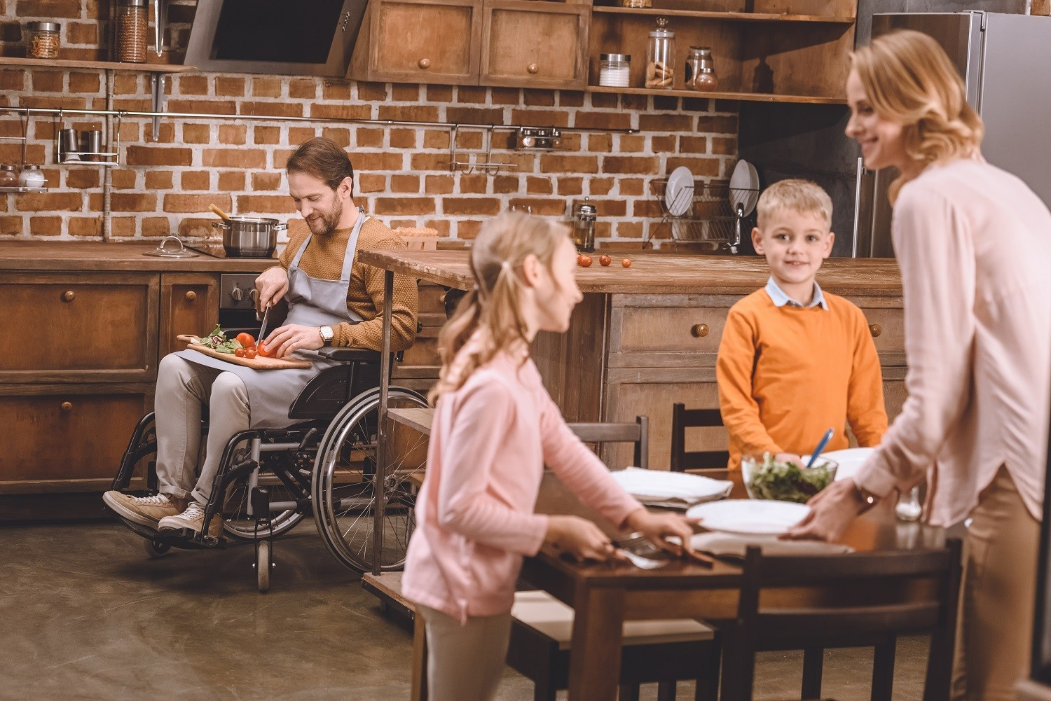 A woman and two children set the table while a man, seated in wheelchair, chops some vegetables