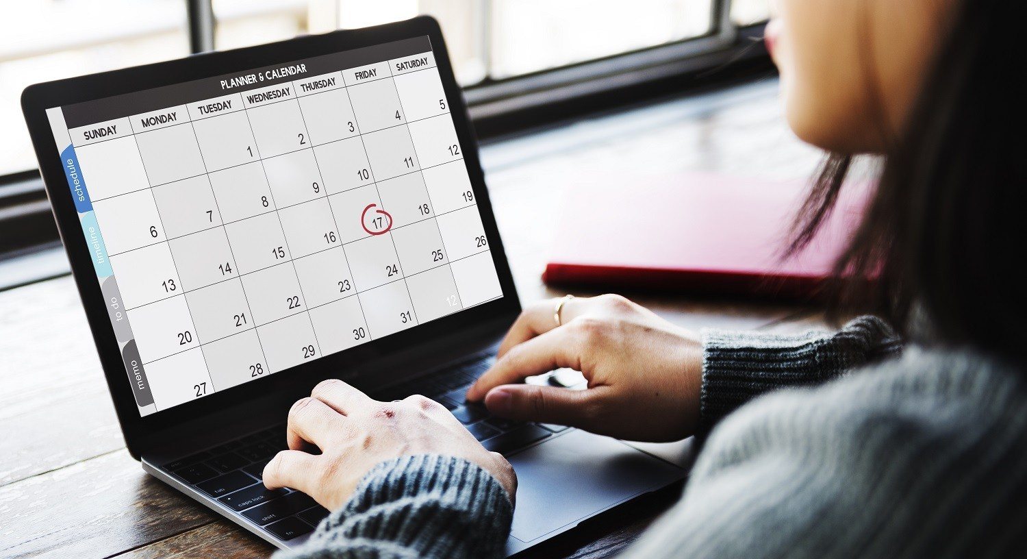 A woman using a calendar on her laptop