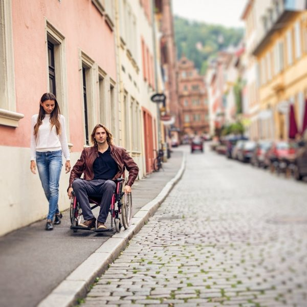 A man in wheelchair on sidewalk with a woman walking beside him