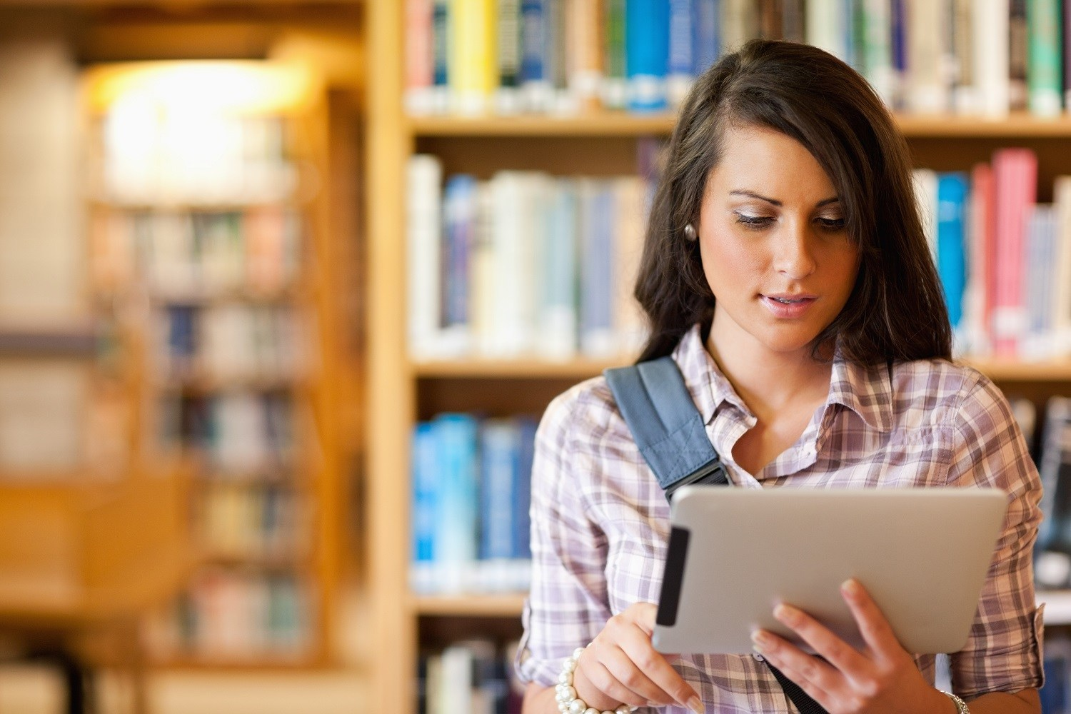 A woman using a tablet in a library