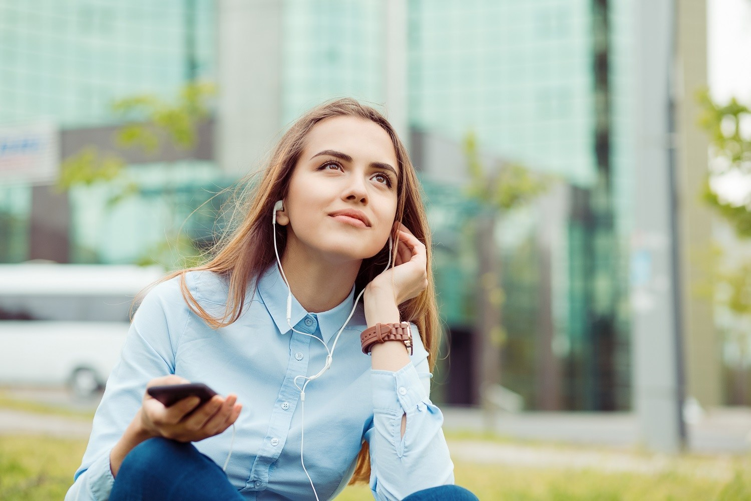 Woman sitting outside with earphones plugged in