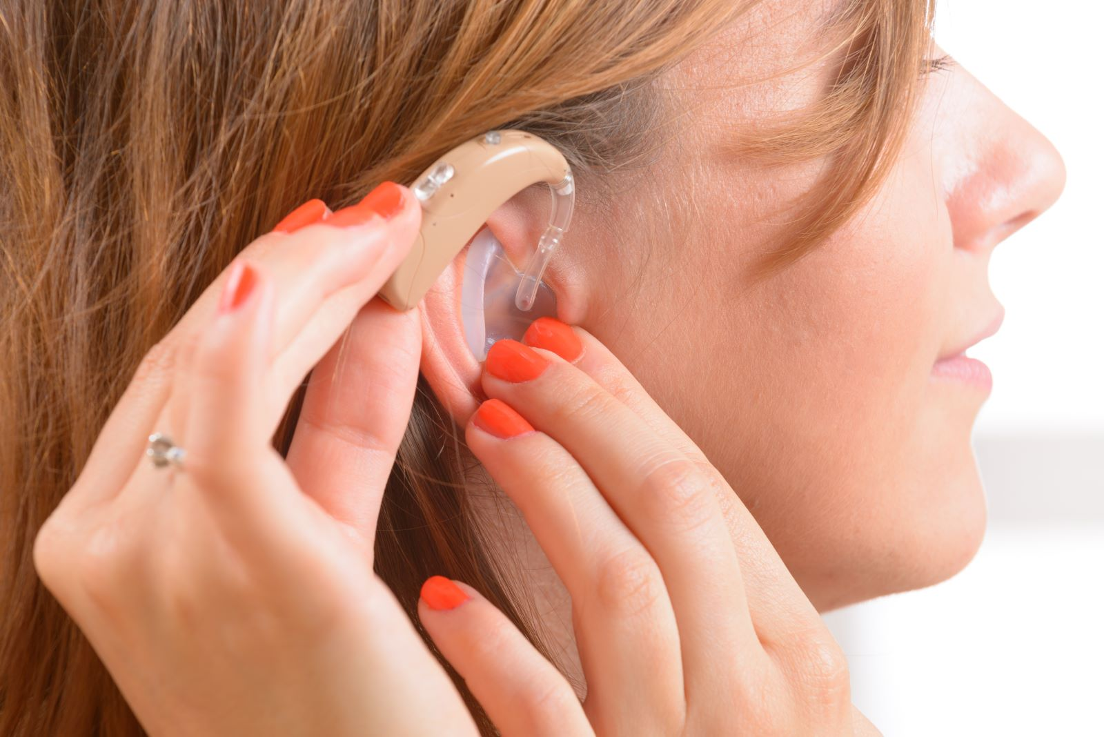 Stock image of a woman putting on a hearing aid