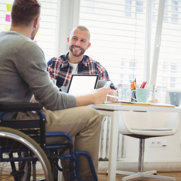 A man in a wheelchair in an office setting in conversation with another man at a desk
