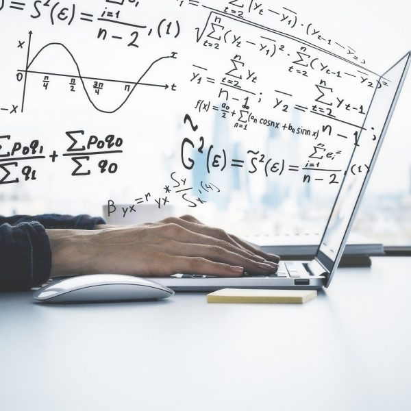 stock image of hands on a laptop with equations coming out of the screen