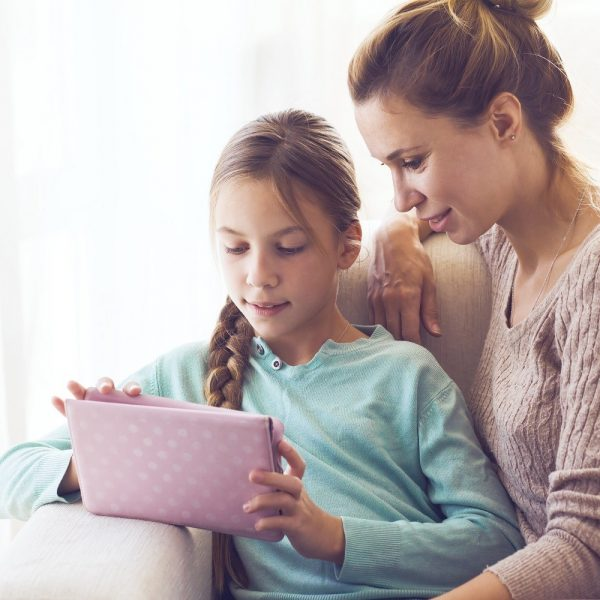 Girl using an iPad, with woman sitting next to her