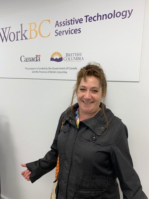 Karen in front of a WorkBC Assistive Technology Services sign