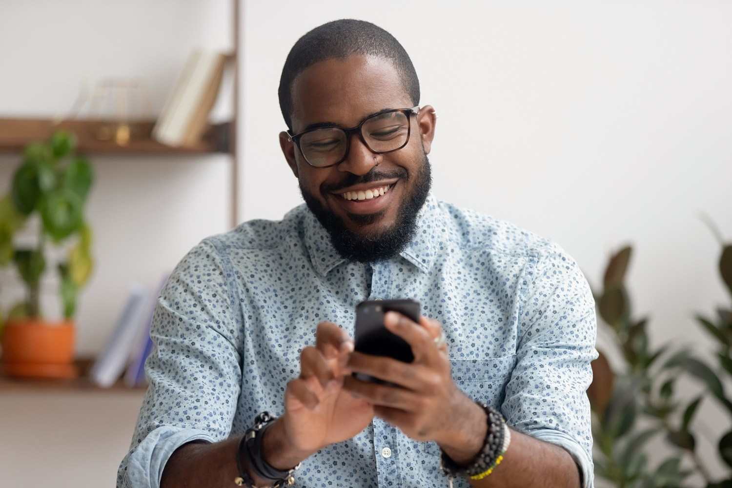 man smiling and using his smartphone