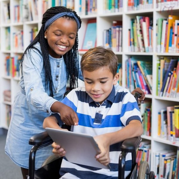Two children in a library. One is holding an iPad and sitting in a wheelchair