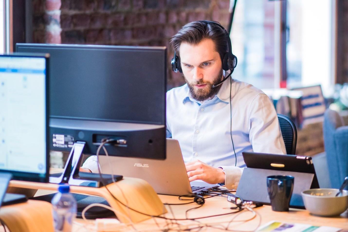 man working at his laptop, wearing headphones