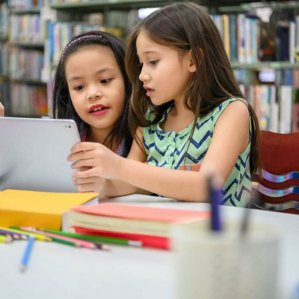 two children looking at an iPad in a library