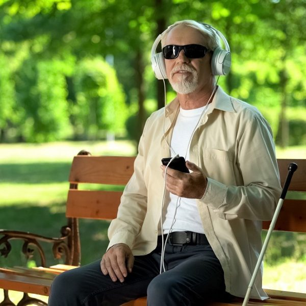 man wearing dark glasses, using headphones with his phone, seated at a park bench