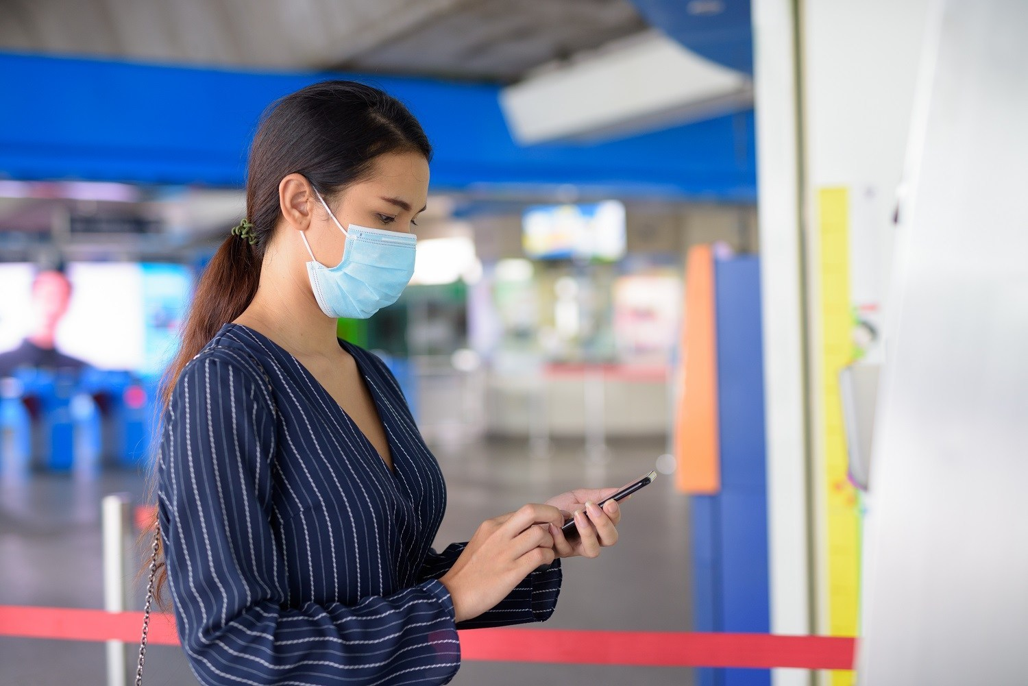 Woman wearing a mask, using her phone
