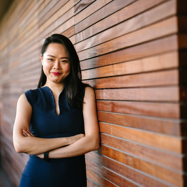 woman standing against a wall, smiling