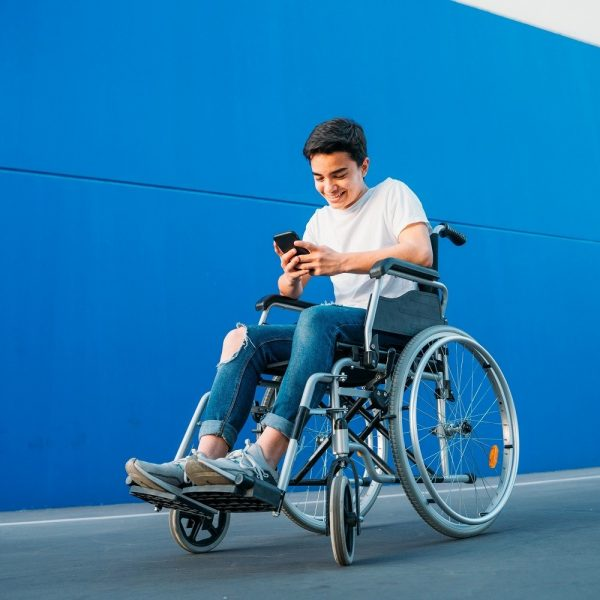 Youth seated in wheelchair, outdoors, using his phone and smiling