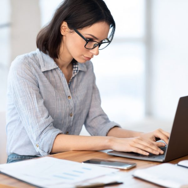 woman typing on her laptop at her desk