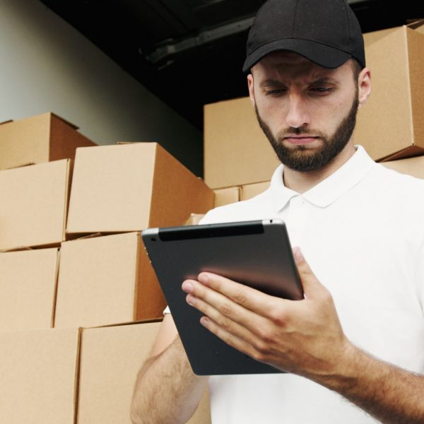 man using a tablet; piles of boxes behind him