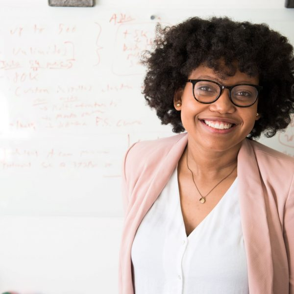 woman smiling; behind her is a whiteboard