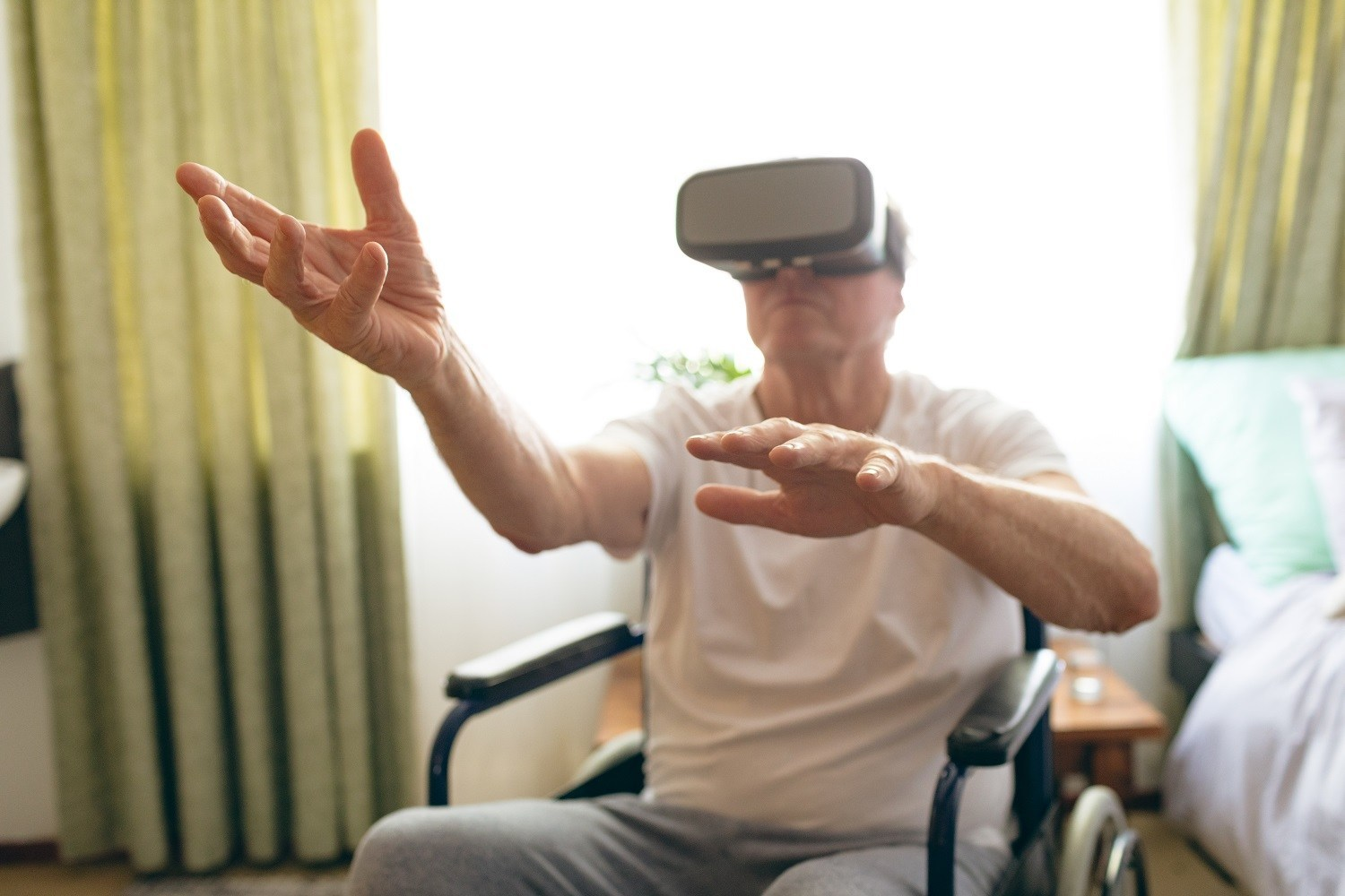 man seated in a wheelchair, using a virtual reality set