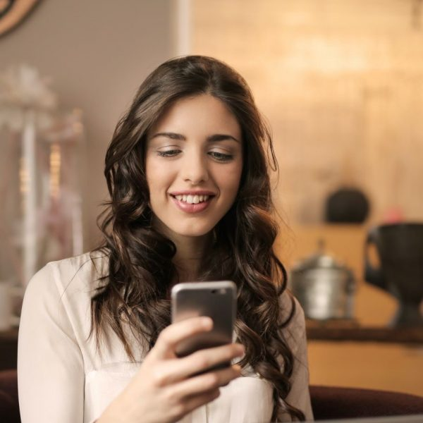 A woman using her phone, smiling
