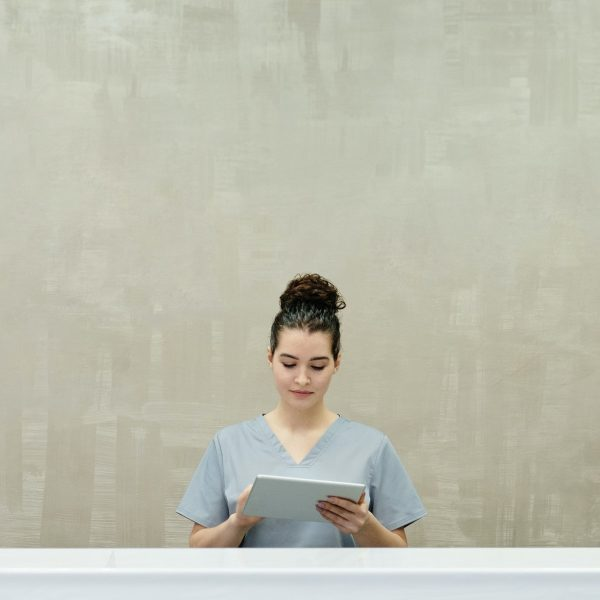 stock image of a woman using a tablet while standing in a hallway