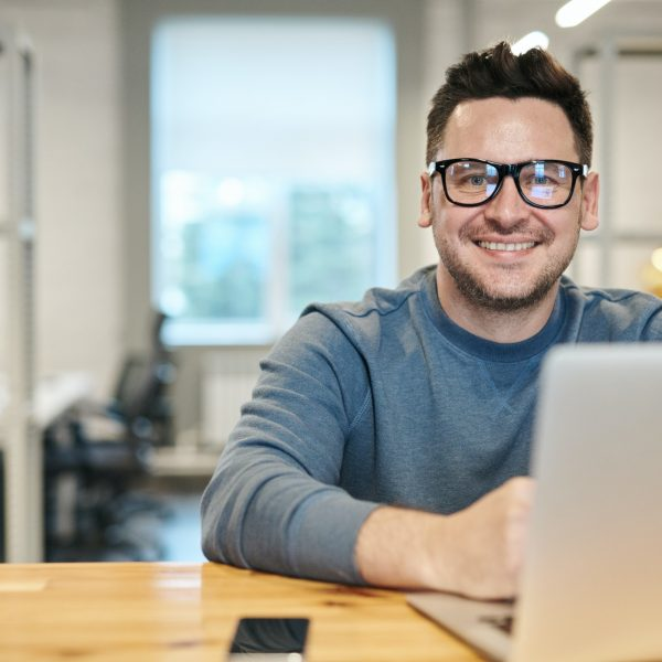 man seated at a desk with his laptop, smiling