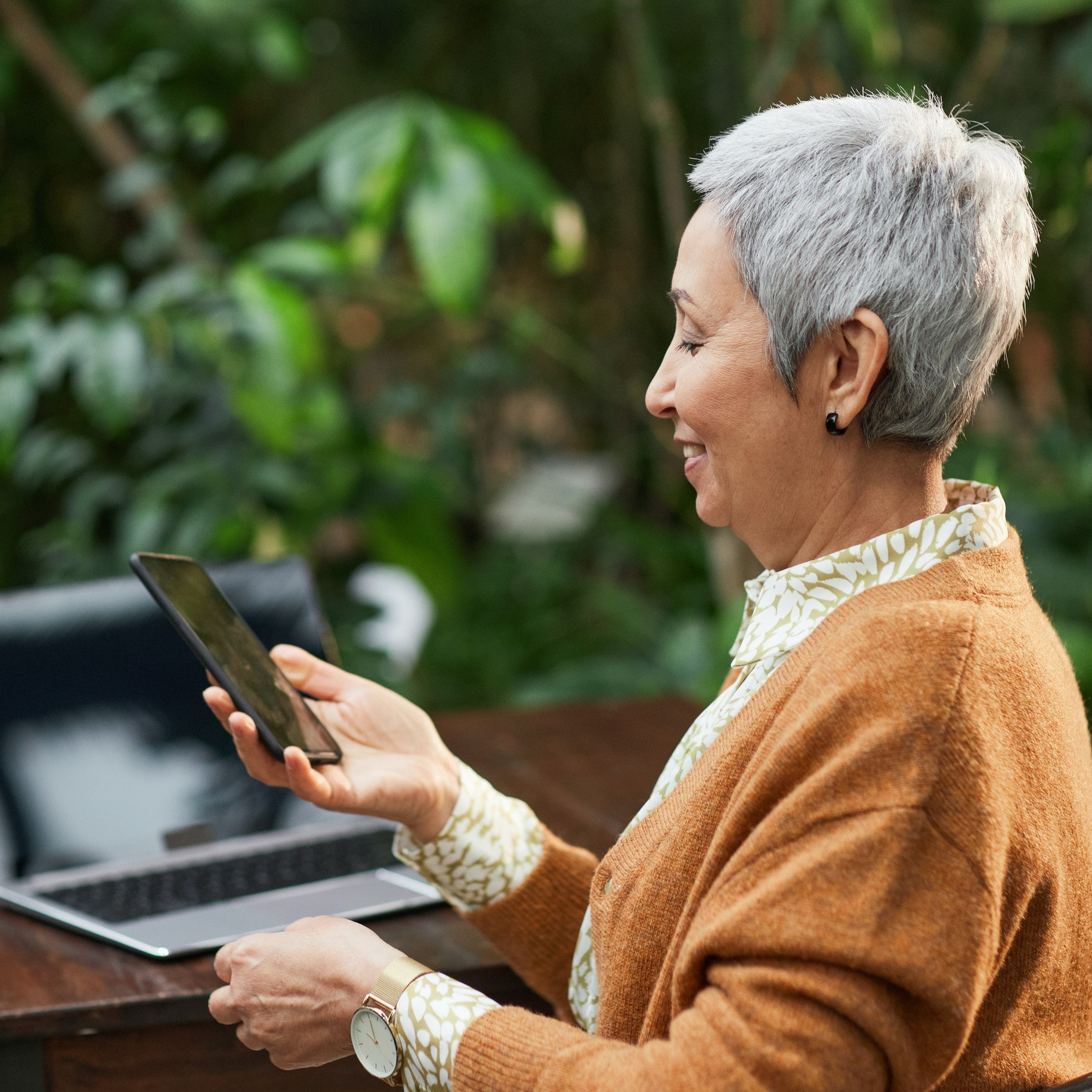 A woman seated outdoors, using a phone. Her laptop is on a table