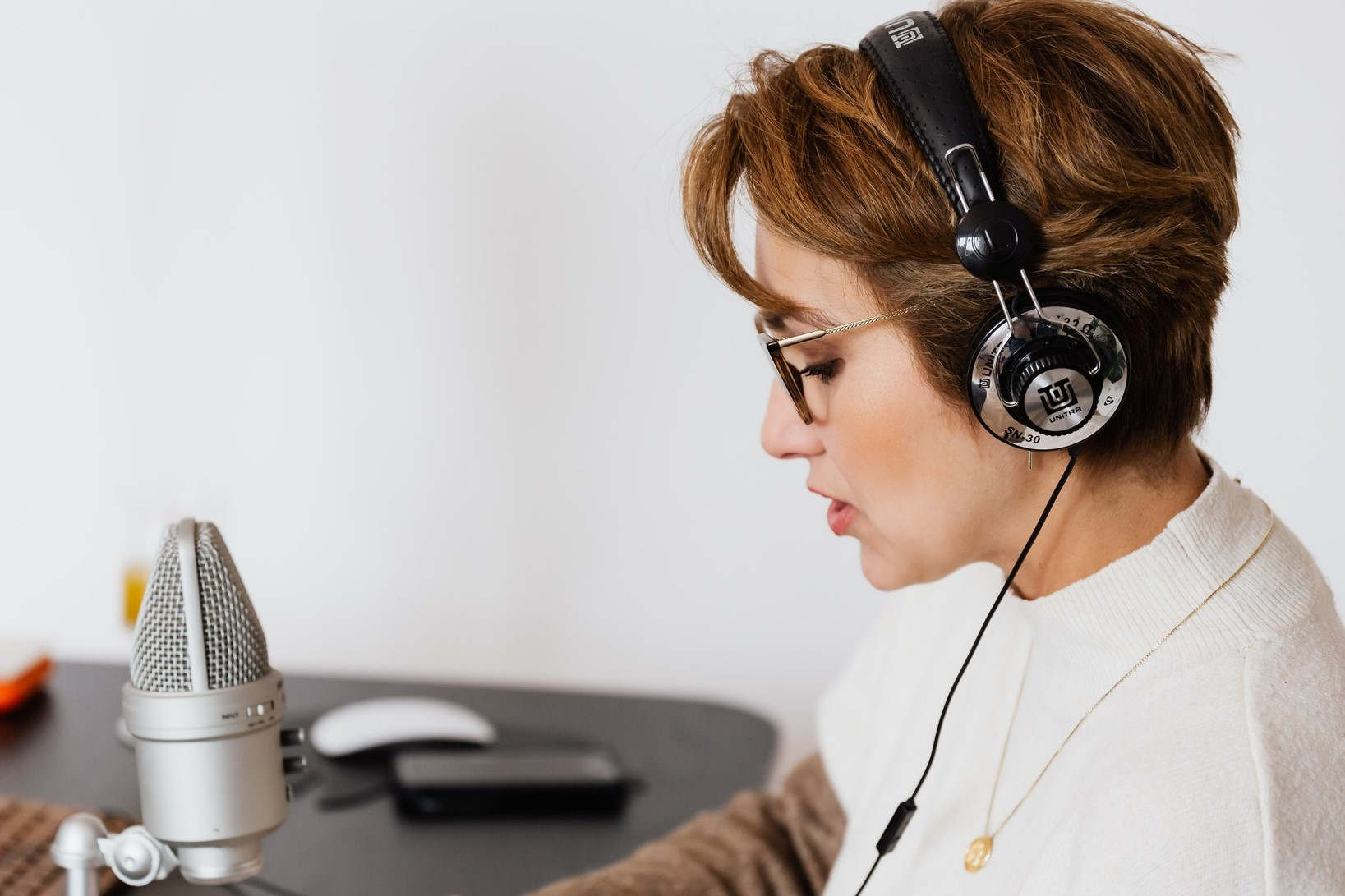 a woman using headphones, singing or speaking into a microphone
