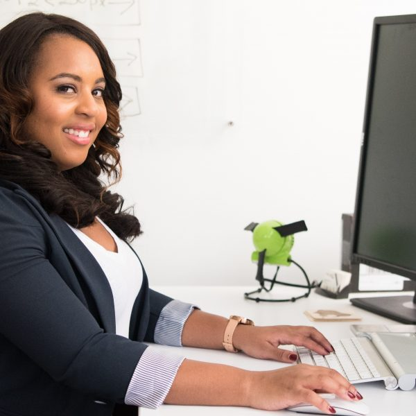 A woman working at a desk, using a keyboard and mouse. She is smiling at the camera