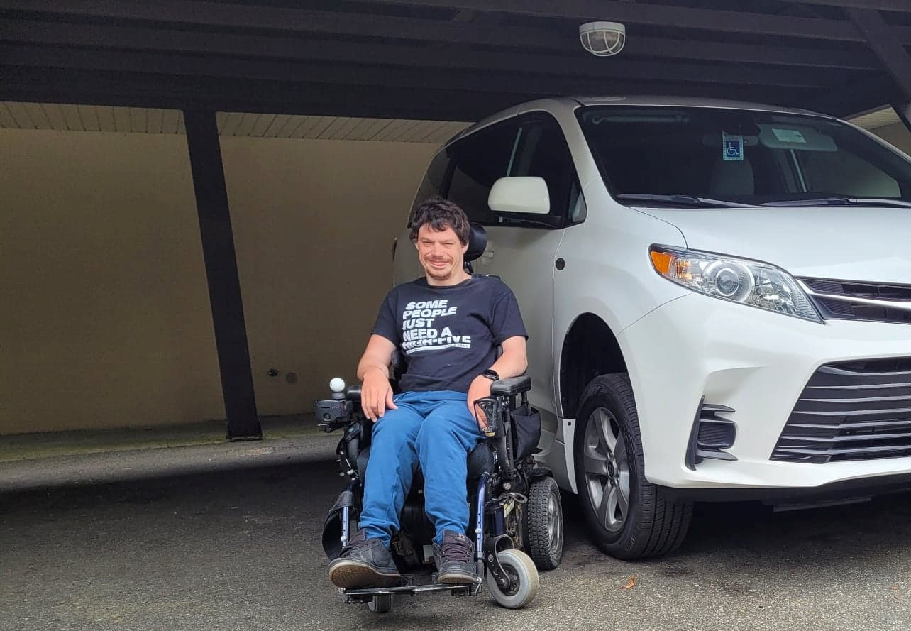 Shayne smiling in front of his modified minivan