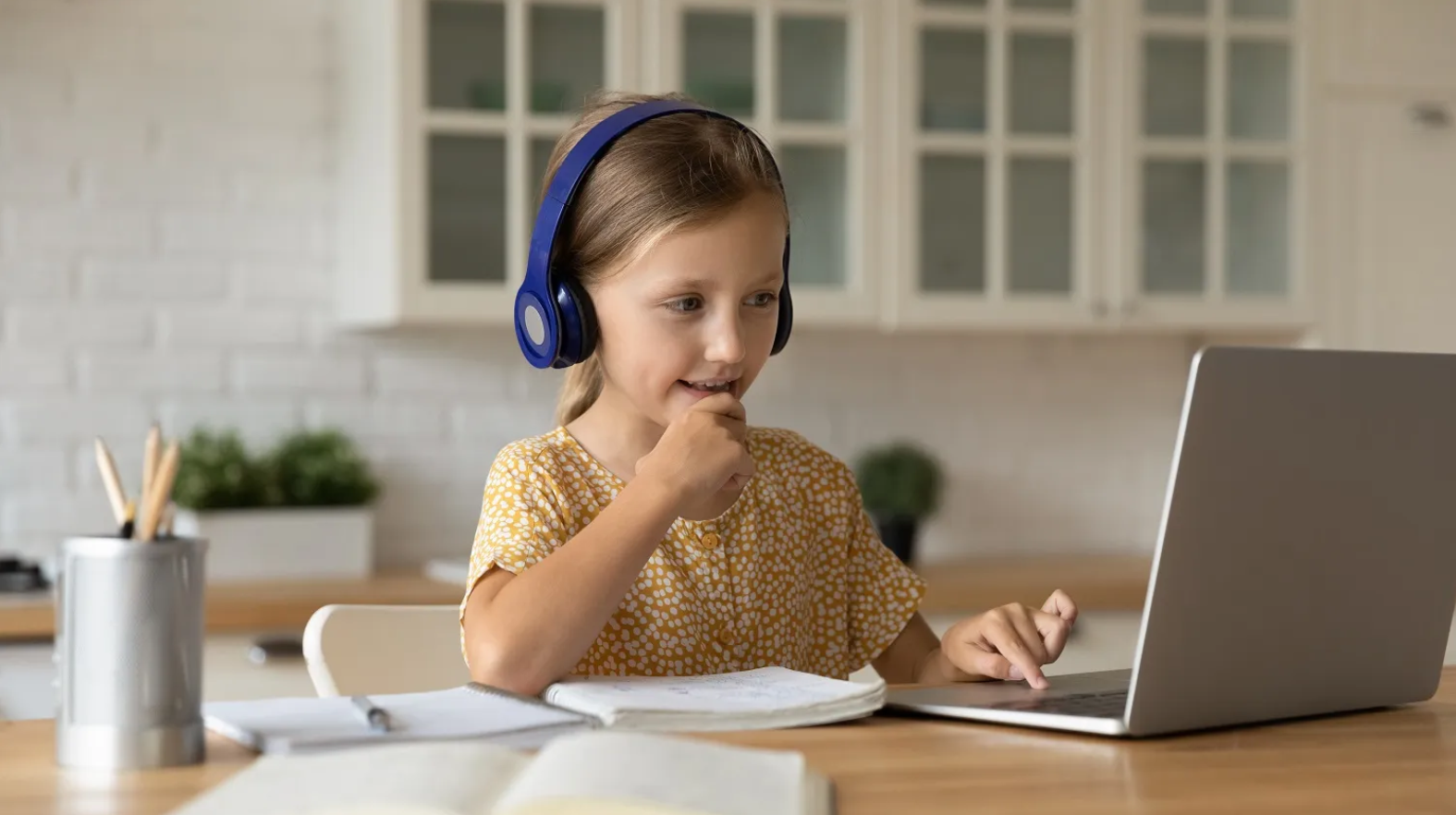 A child using headphones, looking at a laptop, seated at a table
