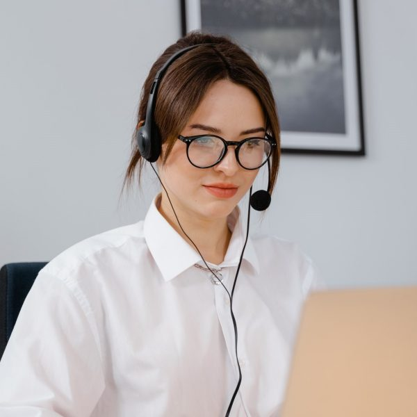 Woman seated at a desk, using headphones while looking at a laptop
